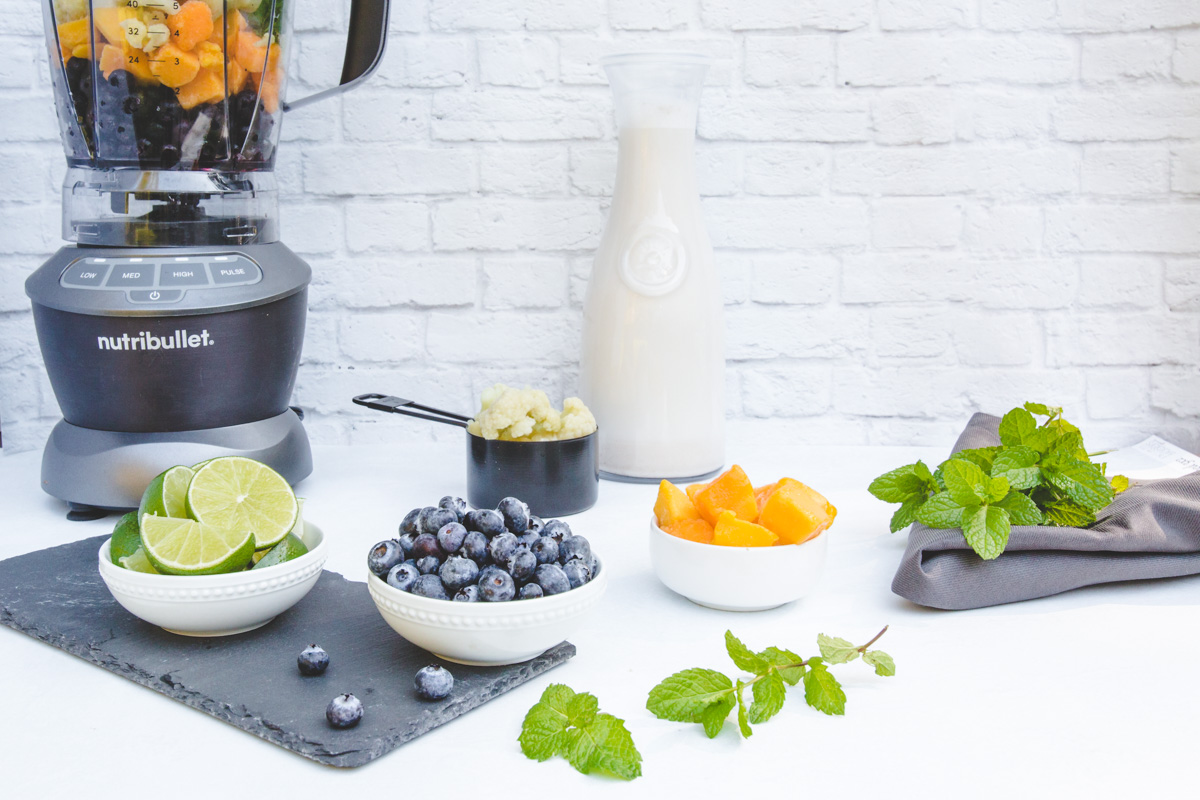 Nutribullet blender with smoothie ingredients laid out next to it.