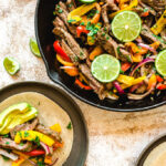 Cast iron skillet and plate with steak fajitas