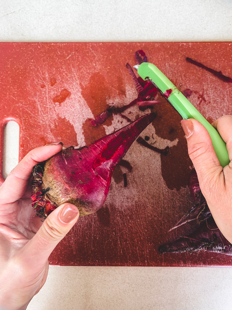 A close-up of hands peeling beets with a vegetable peeler