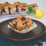 Blueberry muffin on a plate with others in the background