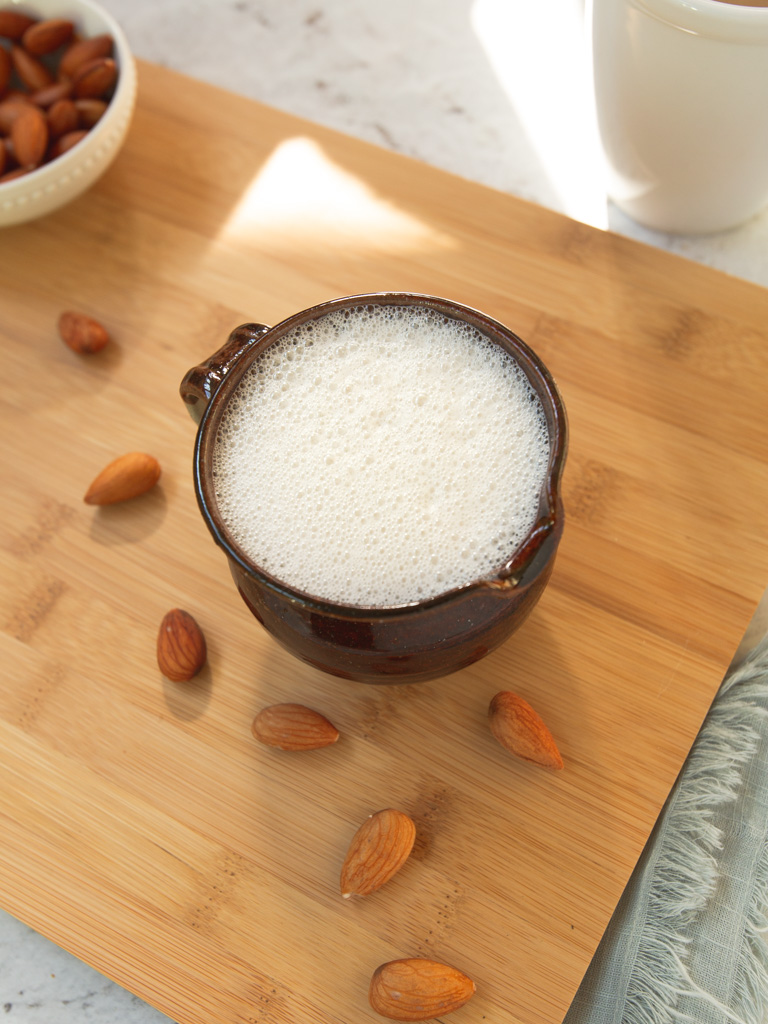 Frothed-up almond milk creamer in a cup with almonds surrounding it.