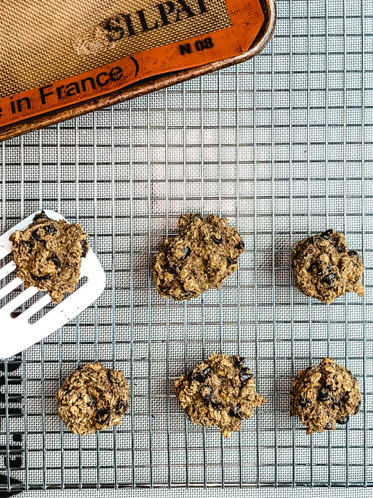 Spatula placing almond pulp cookies on a wire cooling rack