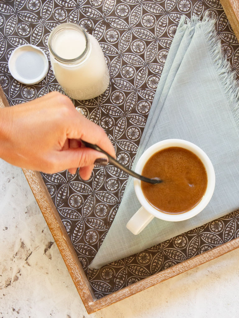 Hand stirring coffee cup on tray